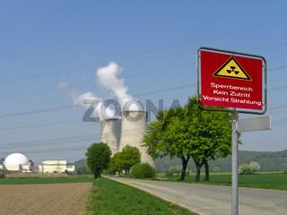 Kühltürme und Reaktorkuppel eines KKW mit aufgehängtem Warnschild