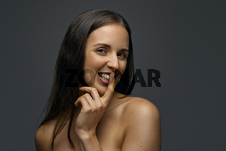 Young tempting woman against dark background