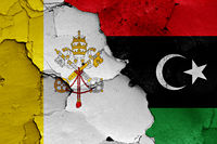 flag of Vatican and Libya painted on cracked wall