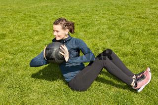 Frau bei Fitnesstraining mit Gewichtsball im Garten