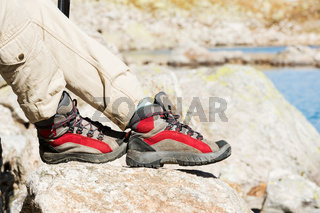 Close-up of female legs in trekking boots against the background of rocks and distant Caucasian lands