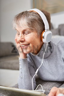 Seniorin hört mit Genuss Musik über Kopfhörer