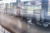 Young woman traveling by train, looking out window while sitting in train.
