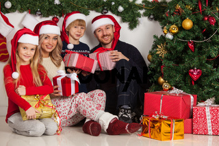 Cheerful family with Christmas gifts