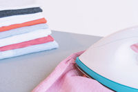 Man ironing blue shirt on ironing board