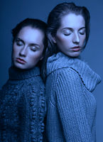 Halloween beauty portrait of two young women in gray sweaters on grey background. Beautiful girls stretching hands forward in embrace. Female friendship concept