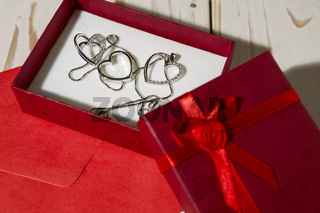Closeup of silver heart pendants in a red gift box and a red envelope
