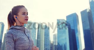 happy woman with earphones running in city