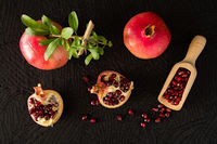 Ripe pomegranate fruits and bailer with seeds inside seen from above