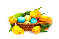 Easter eggs in basket with tulips