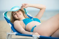 Young lady sunbathing on a beach. Beautiful woman posing at the