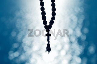 Church beads with a cross on a soft bokeh background