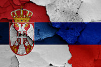 flags of Serbia and Russia painted on cracked wall