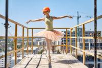Ballerina posing at concrete balcony