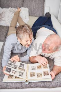 Paar Senioren betrachtet Fotos im Fotoalbum