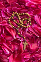 Rosary beads on flower background.
