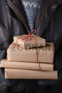 Man holding a stack of plain paper wrapped christmas gifts