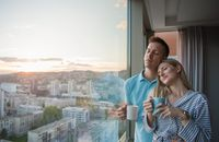 young couple enjoying evening coffee by the window