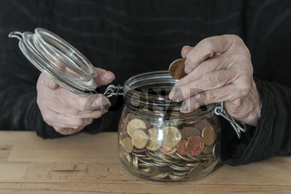 Haende halten ein Einmachglas mit Kleingeld