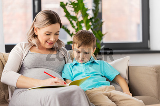 pregnant mother with workbook and son at home