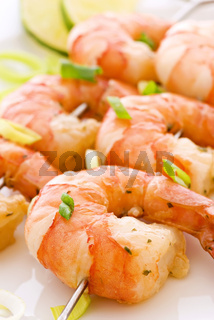 Prawn skewer with king prawns and leek as closeup on a white plate