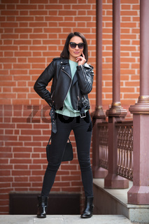 Young fashion woman in black leather jacket walking in city street