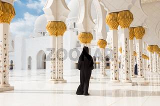 Arabic woman in black burka in Sheikh Zayed Grand Mosque, Abu Dhabi, UAE.
