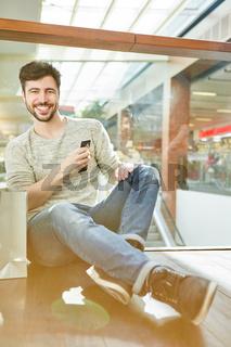 Lächelnder junger Mann macht online Shopping