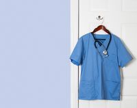 Blue scrubs shirt for medical professional hanging on door