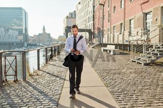 Junger Business Mann nutzt sein Smartphone