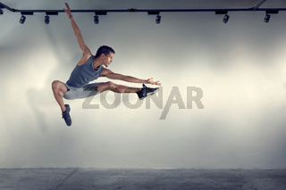 Young man jumping in front of gray wall