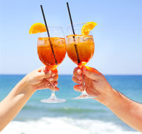 Two cocktail glasses in the hands on sea background
