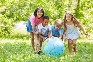 Kinder rollen zusammen Weltkugel übers Gras