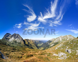 Great clear view in the mountain with beautiful clouds. Alps.