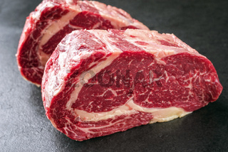 Two raw dry aged Kobe Entrecote Steak as close-up on a slate