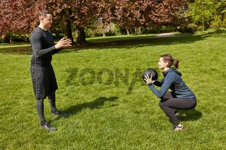 Frau trainiert mit Personal Trainer und Gewichtsball