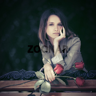 Sad young fashion woman with red roses outdoor