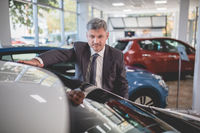 Vehicle manager in auto showroom.