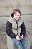 7 year old boy with smartphone outdoors in winter
