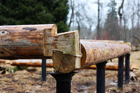 Assembling a wooden frame and building a house. Russia. Texture of old wooden logs and metal columnar base