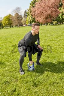Mann macht Kettlebell Fitnesstraining im Park
