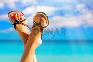 woman feet crossed with paradise island on background