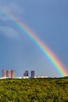 rainbow in dark blue sky over city and urban park