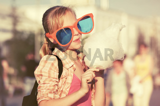 Happy teen girl in sunglasses eating cotton candy walking in city street