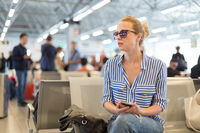 Woman using her cell phone while waiting to board a plane at departure gates at international airport.