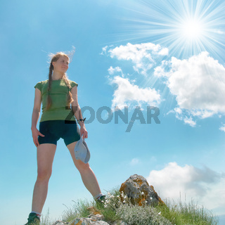 Happy woman on the top of a mountain