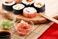Composition with assorted sushi rolls and bowls of spices