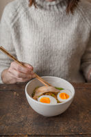 Woman eating Asian soup Ramen with chicken