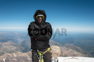 a mountaineer in a ski mask and a down jacket with a hood that is cold on top of the mountain.
