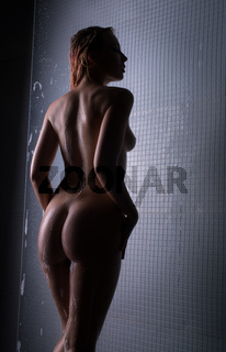 Naked blonde having shower cropped rearview
